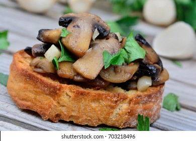 Bruschetta with mushroom garlic and parsley on wooden table