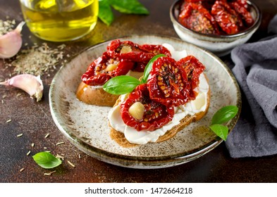 Bruschetta with olive oil, sundried tomatoes, cottage cheese and fresh basil. Tasty savory Italian appetizers