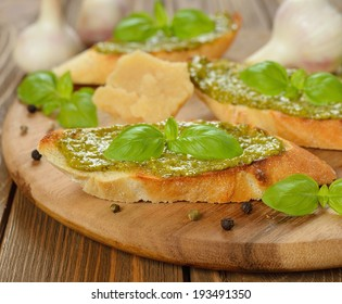 Bruschetta with pesto and basil on a brown background