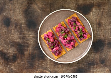 Bruschetta with pickled beet, apple and mayonnaise. Sandwich or crostini on a serving plate on a brown background. Crusty bread with traditional Scandinavian beetroot salad