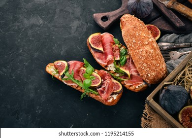 Bruschetta with prosciutto, fresh figs and cheese. On the old background. Healthy food. Free space for text. Top view.