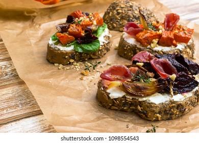 Bruschetta with pumpkin, prosciutto, cream cheese and onion
