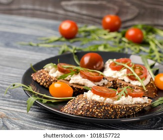 Bruschetta with ricotta cheese, tomatoes and arugula on the plate. Wooden rustic table.  Close-up, place for text. Selective focus.