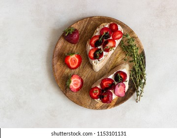 Bruschetta or sandwich with strawberries, cream cheese or ricotta, balsamic vinegar and thyme on a light background. Summer snack food. Italian breakfast. Italian cuisine.