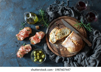 Bruschetta set with ciabatta bread, olive oil and ham for wine on dark table. Top view with copy space. - Shutterstock ID 1987607447