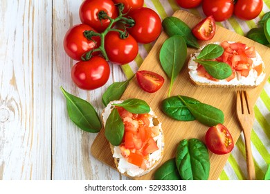 Bruschetta with spinach and cherry tomatoes on slices of toasted baguette or ciabatta. Traditional Italian appetizers. European cuisine.