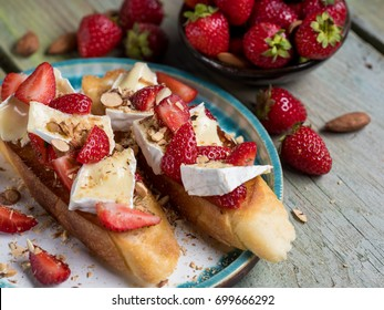 Bruschetta with strawberry, nuts and cheese camembert on wooden blue rustic background. Top side view, selective focus, close up.