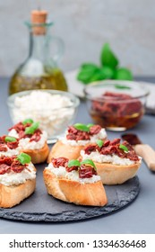 Bruschetta with sun dried tomato, feta and philadelphia cheese and basil on a stone plate, vertical
