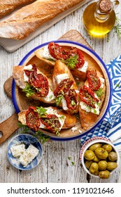 Bruschetta, toasted slices of bread with feta cheese, dried tomatoes, olive oil and fresh aromatic herbs, on a plate on a wooden table, top view. Delicious Mediterranean vegetarian   appetizer