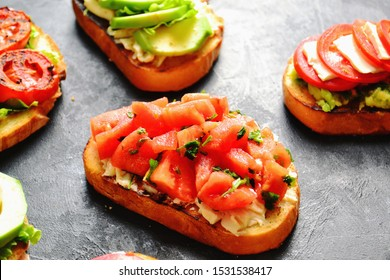 Bruschetta with tomatoes, avocado, cheese, grilled tomatoes. Delicious sandwiches and toasts. Vegetarian wholesome food. Bruschettas on a dark background.