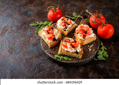 Bruschetta with tomatoes, mascarpone cheese and balsamic sauce on wooden cutting board on dark background