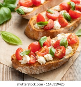 Bruschetta with tomatoes, mozzarella cheese and basil on a old rustic table. Traditional italian appetizer or snack, antipasto