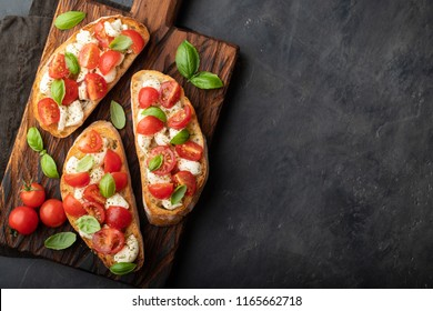 Bruschetta with tomatoes, mozzarella cheese and basil on a cutting board. Traditional italian appetizer or snack, antipasto. Top view with copy space. Flat lay