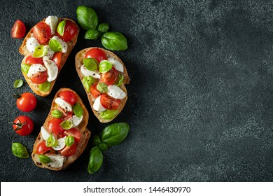 Bruschetta with tomatoes, mozzarella cheese and basil on a dark background. Traditional italian appetizer or snack, antipasto. Top view with copy space. Flat lay