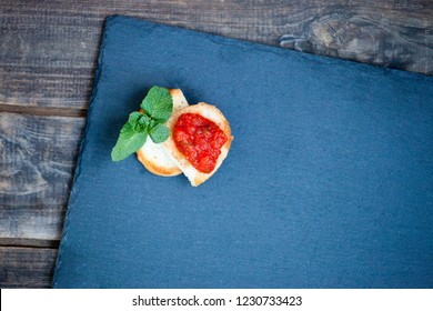 Bruschetta with tomatoes on a slate plate. Italian style antipasto appetizer. Copy space
