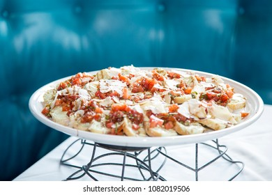 bruschetta with tomatoes and parmesan cheese on white plate with blue background