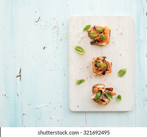 Bruschettas with Prosciutto, roasted melon, soft cheese and basil on white wooden serving board over light blue background, top view, copy space