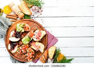 Bruschetti with bacon, salted fish, cheese and vegetables. Set bruschetta. Top view. Free copy space.