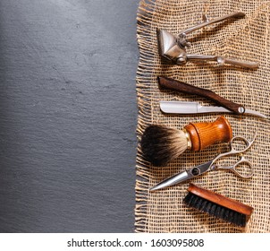 a brush, a barber brush, hairdressing scissors, a razor and an old, retro manual shaver. Tools of a barbershop. accessories. all about sackcloth and slate stone. with negative space to write