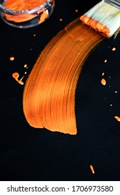 With a brush, a brightly glowing stripe of orange paint was painted - low depth of field in an abstract painting to art and paint