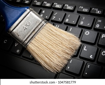 The brush cleans the computer keyboard as a concept of maintaining digital data.