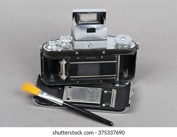 a brush and dusty old photo camera with open back cover