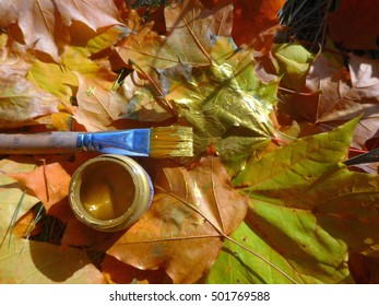 Brush with gold paint on the background of the fallen leaves