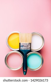 Brush with green handle on open cans of paint on pink pastel background. Yellow, white, pink, turquoise colors. Renovation concept.