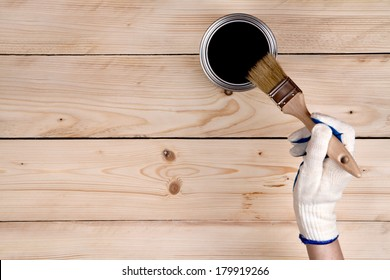 Brush in hand and painting on the wooden wall