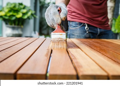 Brush in hand and painting on the wooden table