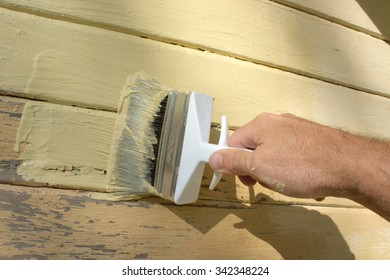 Brush in a hand painting a wall