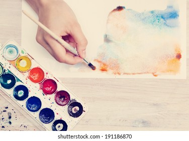 brush in the hands of the artist, watercolor painting, creativity, with retro effect