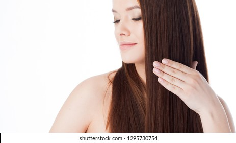 Brush her hair. Attractive girl with long hair. Portrait of a beautiful young woman using a comb. White background