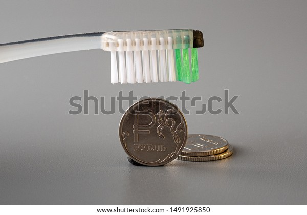 the brush hovered over a metal coin on a gray background. even lay two coins