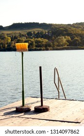 A brush instead of an umbrella on wooden platform by the lake. Practicality and misuse concept.