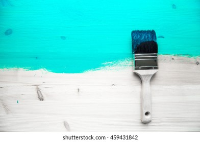 Brush with light blue paint on light wooden painted background