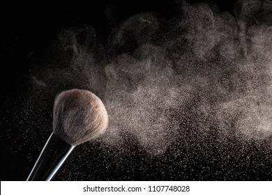 Brush for makeup with flying around powder is isolated on a black background.