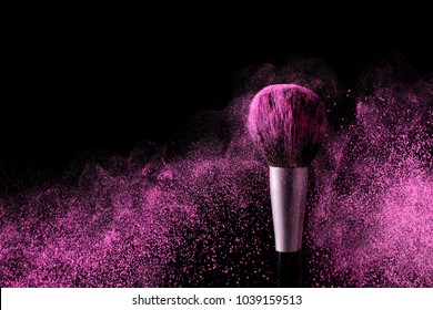 Brush for makeup with purple make-up shadows in motion on a black background.