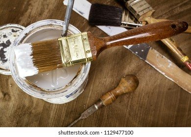 Brush on top of an open can of white paint