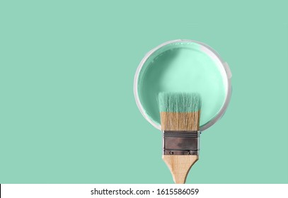 The brush in the paint color of neo mint and the can with paint color neo mint over neo mint background. Copy space text.