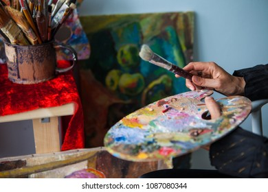 Brush and palette in hands, against the backdrop of an art workshop.