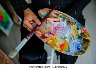 Brush and palette with mixed colors in hands on a black background.