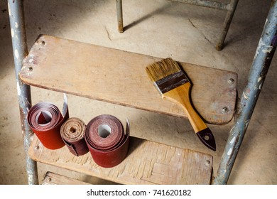 Brush and sandpaper  on the stair of ladder in apartment during the remodeling, renovation, extension, restoration, reconstruction and construction