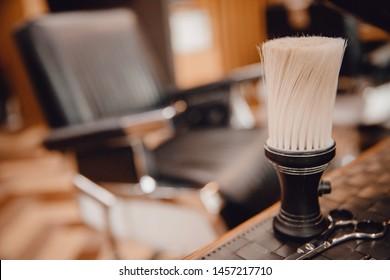 Brush for shaving beard along with bowl, blurred background of hair salon for men, barber shop.