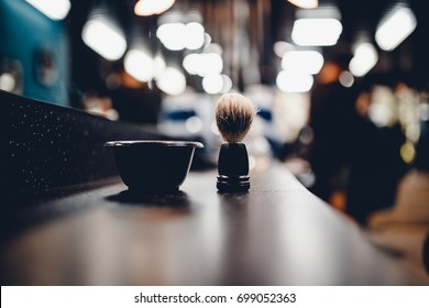 brush for shaving a beard along with a bowl, a blurred background of a hair salon for men, a barber shop