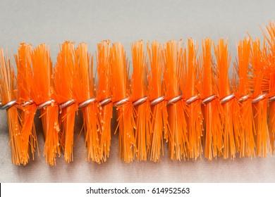 Brush for washing bottles, orange abstract background.