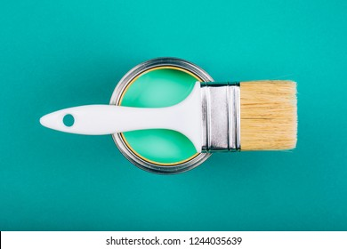 Brush with white handle on open can with turquoise color of paint on blue background. Renovation concept.