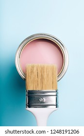 Brush with white handle on open can of pink paint on blue pastel background. Renovation concept. Macro.