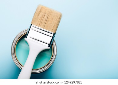 Brush with white handle on open can of turquoise paint on blue pastel background. Renovation concept. Place for text.