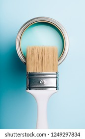 Brush with white handle on open can of turquoise paint on blue pastel background. Renovation concept. Macro.